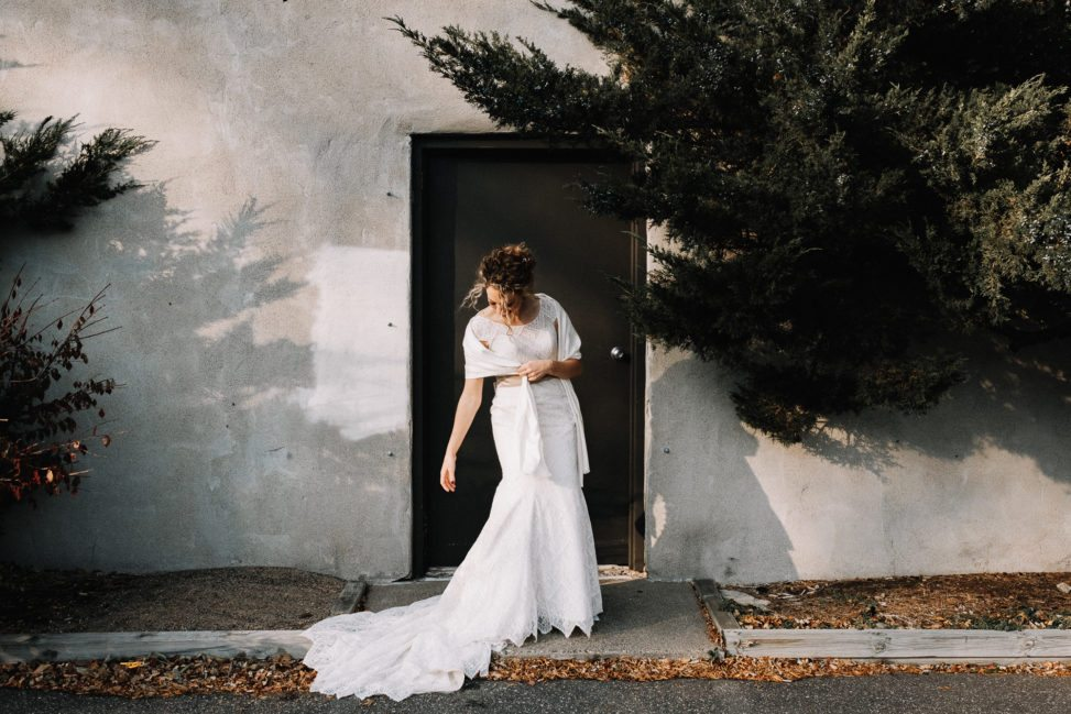 a bride looks downward as her dress train is in the gutter
