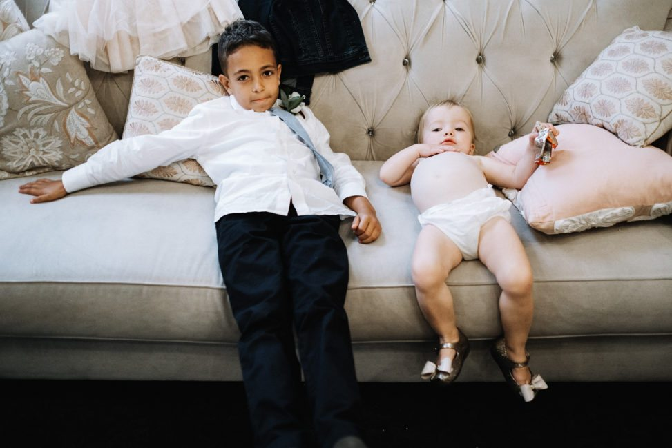 a young child in a tie and untucked shirt and a baby in a diaper and silver bowed mary janes lie on a couch looking spent