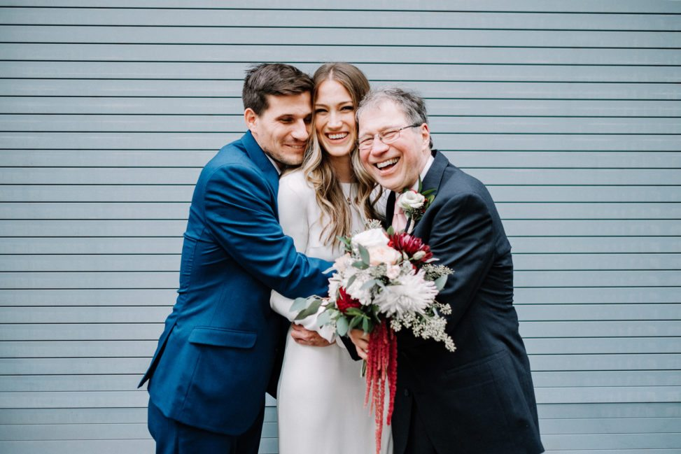 A woman is hugged on both sides by two men.