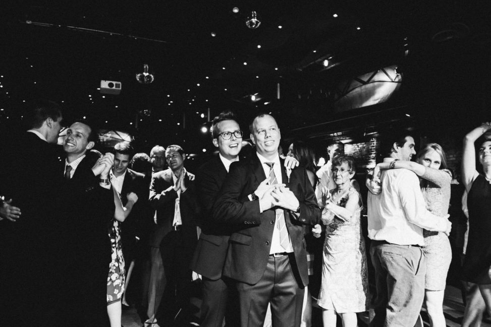 two men look on during a wedding reception