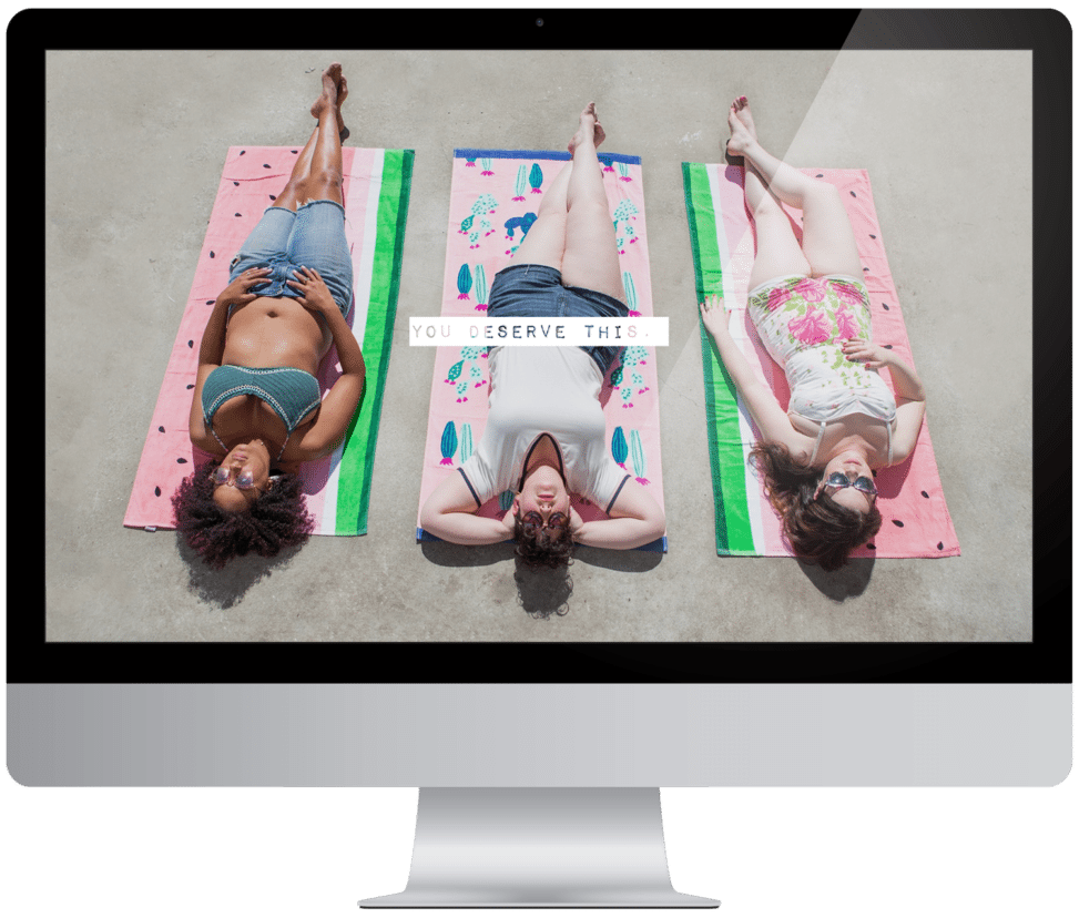 Three women laying out in the sun on beach towels