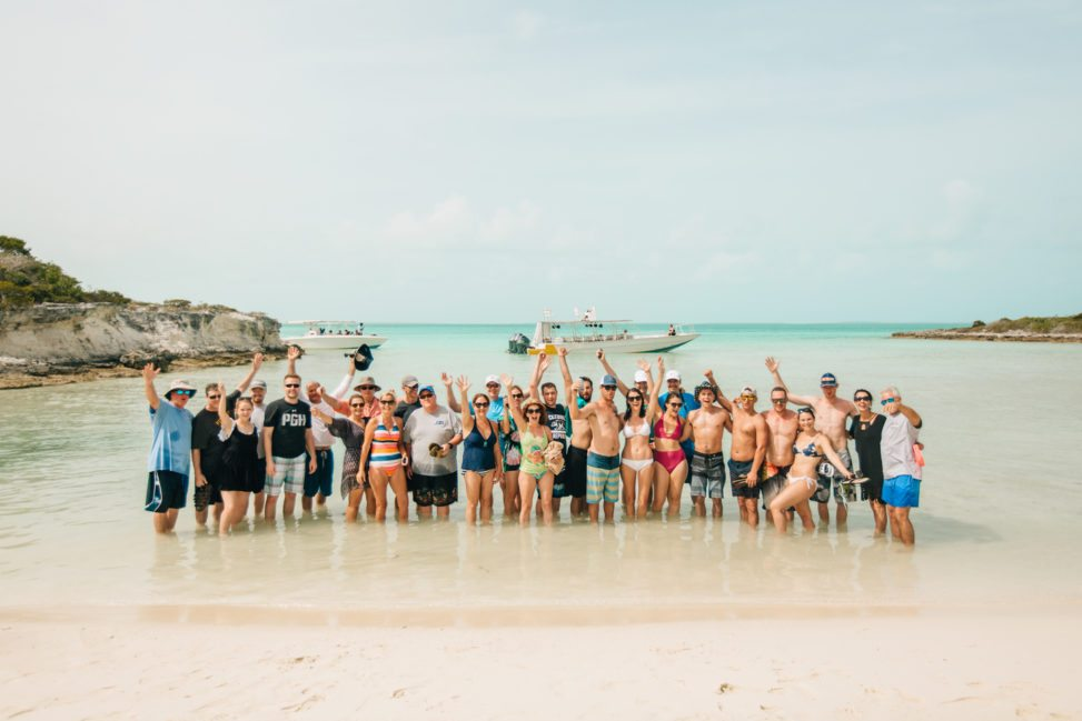 a large group of people stand on the beach and raise their arms overhead