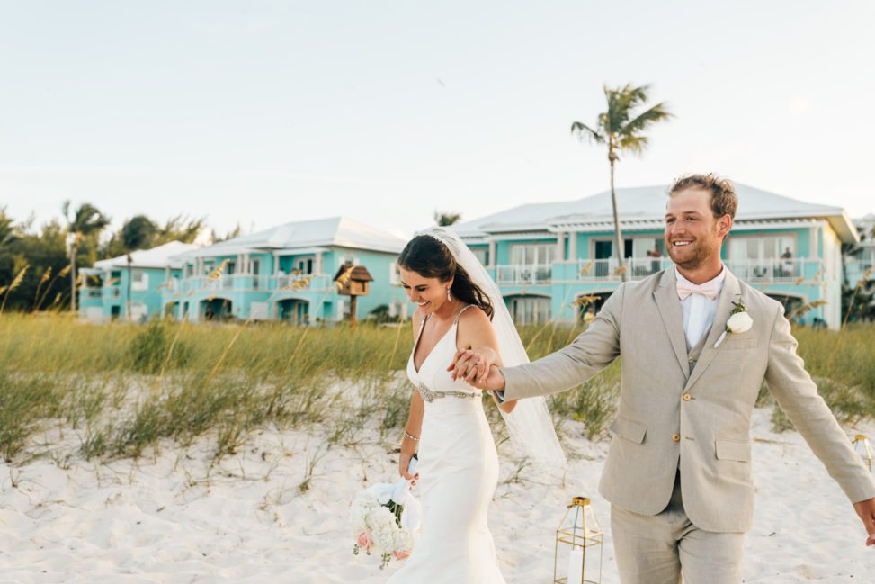 a man and woman walk on the beach on their wedding day