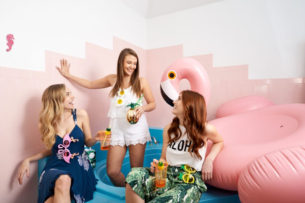 a group of women stand together and hangout with a giant inflatable flamingo