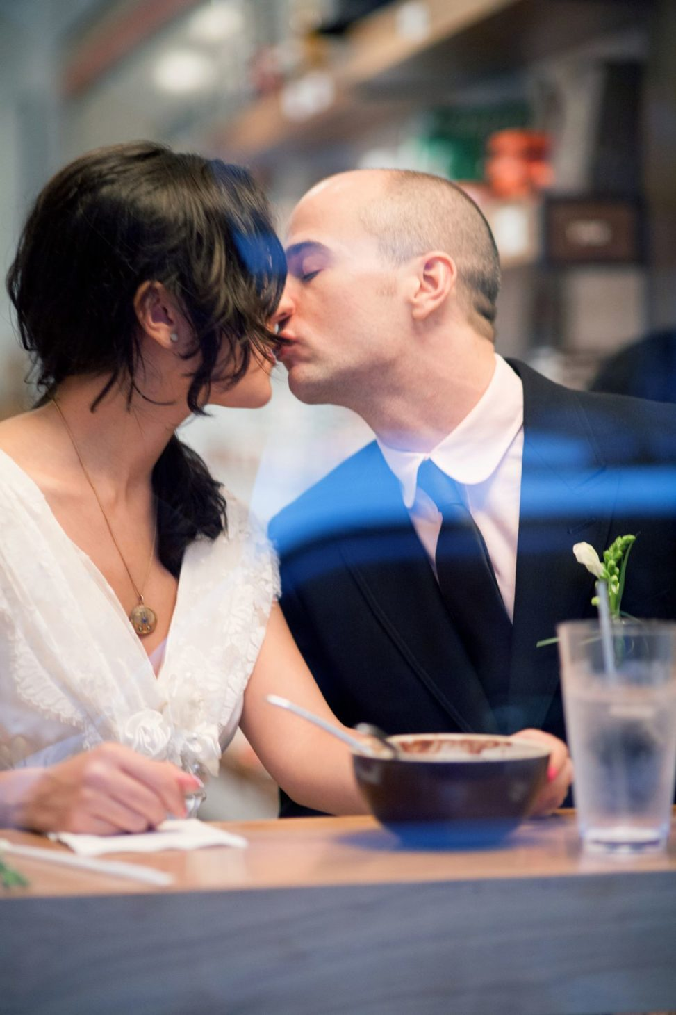 a couple kiss over a bowl of cereal