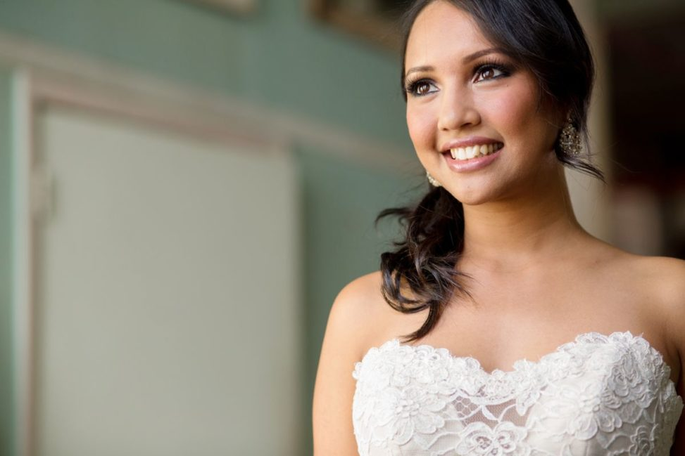 a bride smiles at the window
