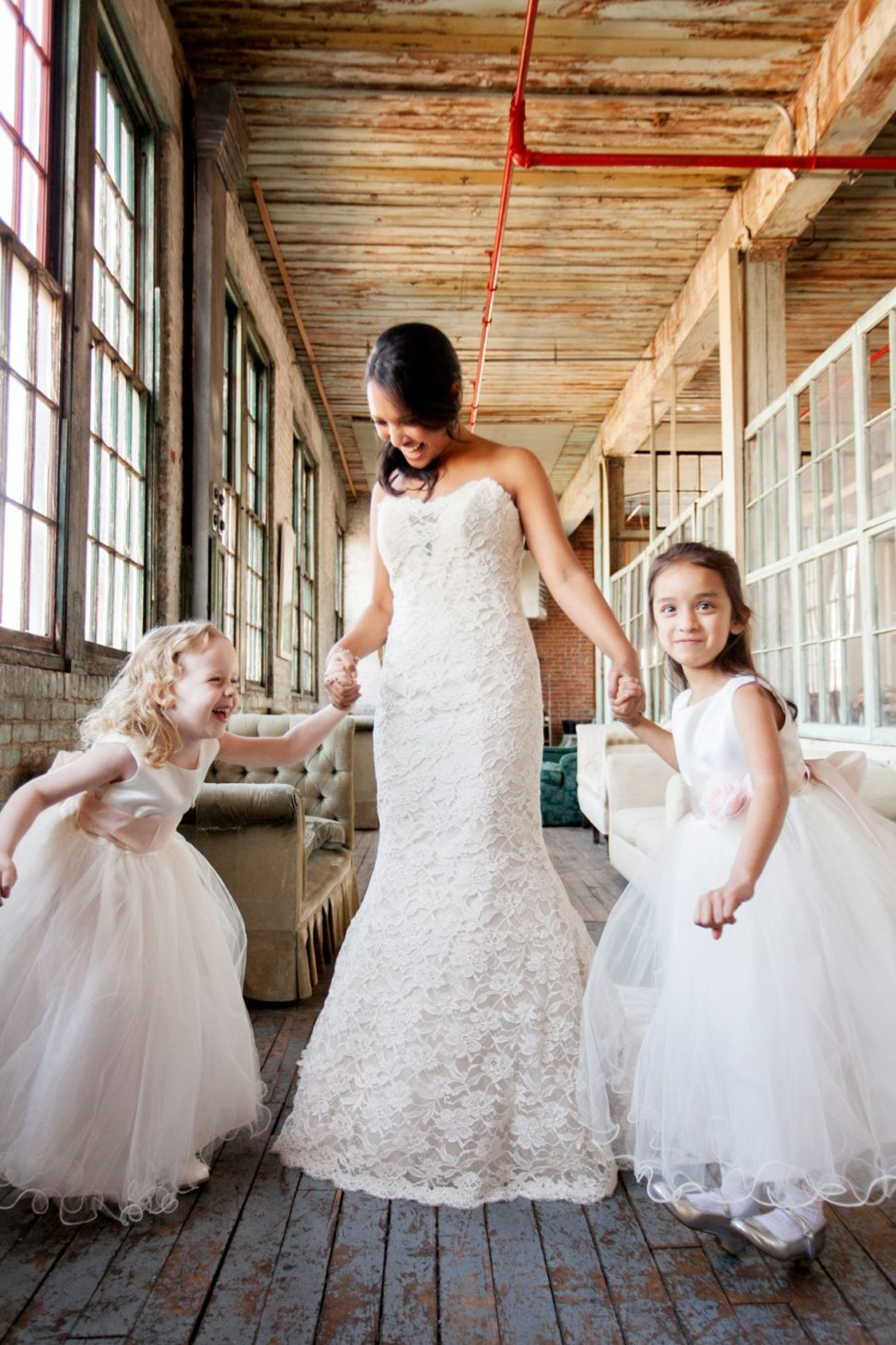 a bride dances with her flower girls