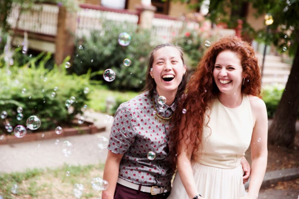 two women smile and laugh while bombarded with bubbles