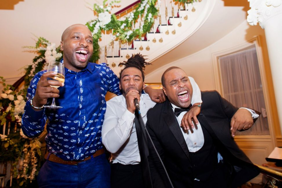 men dance and sing during a reception
