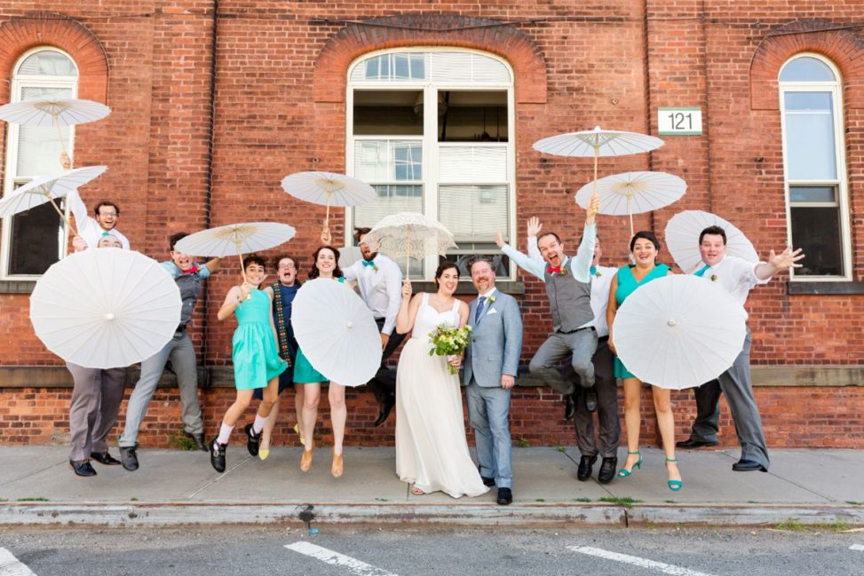 a wedding party jumps in the air with umbrellas