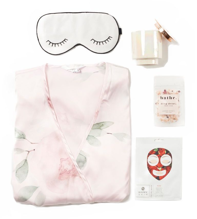 A collection of items including a sleep mask, and pink pajamas