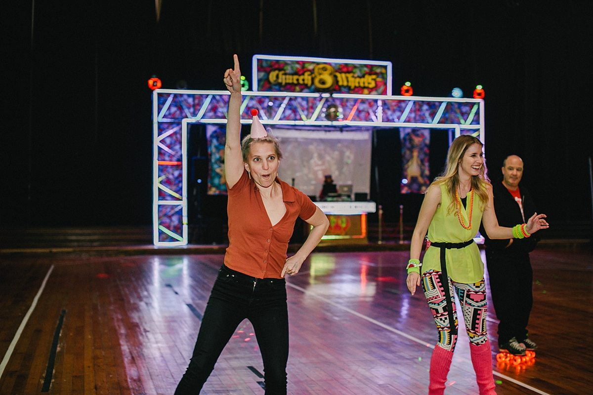 a woman roller skates and does a Saturday Night Fever move