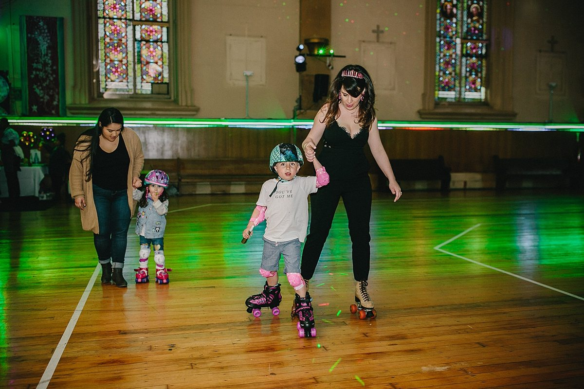 two women hold hands of children as the roller skate