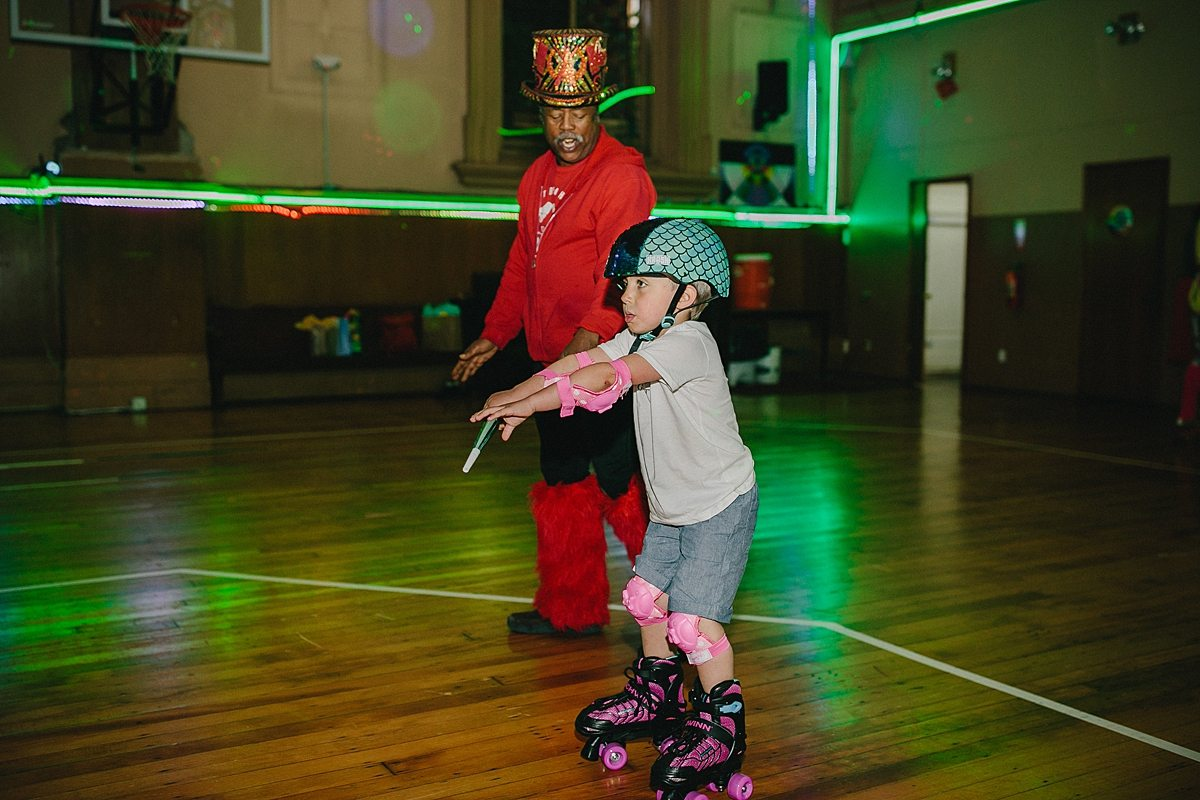 an older gentleman roller skates with a young child