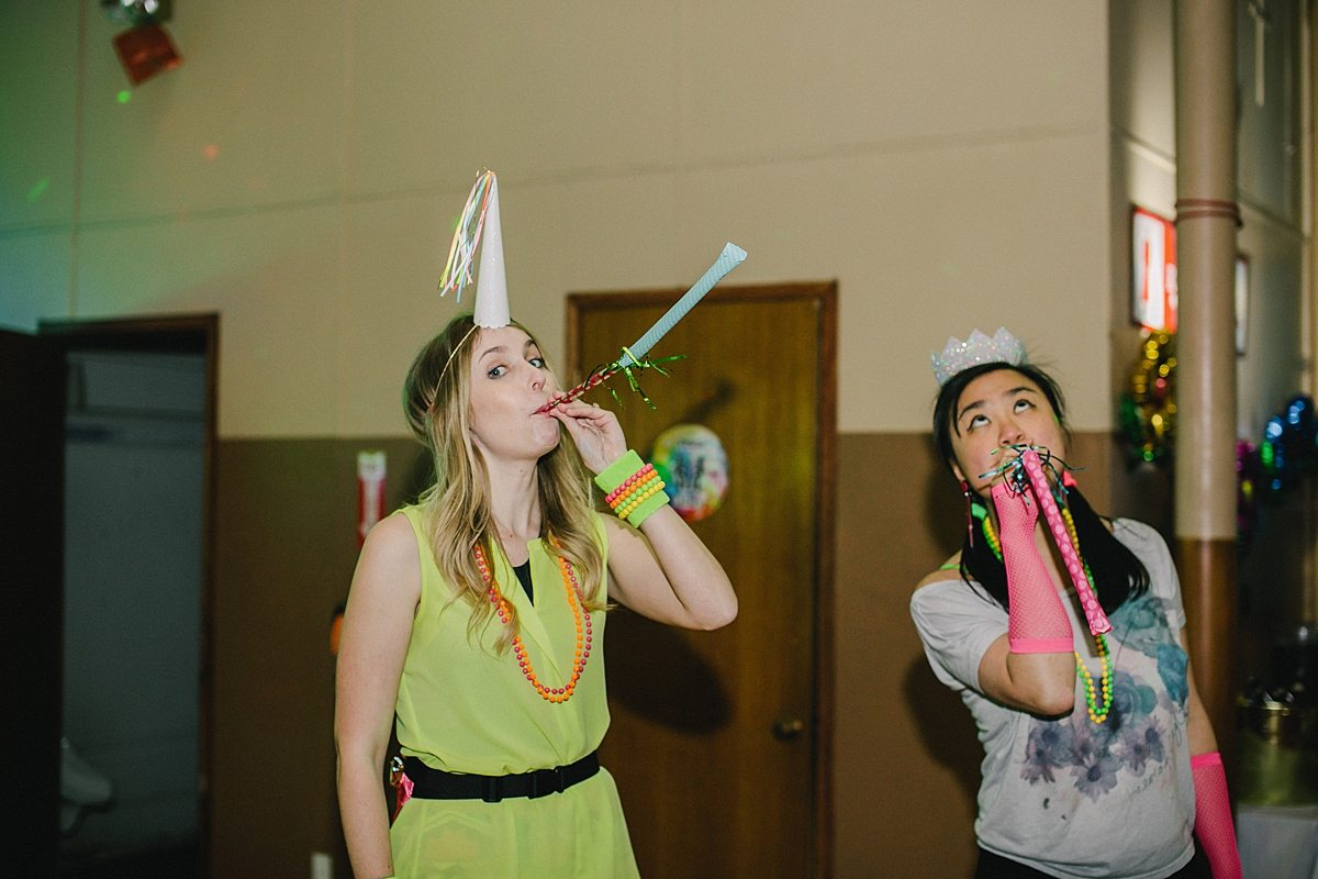 two women blow party blowers
