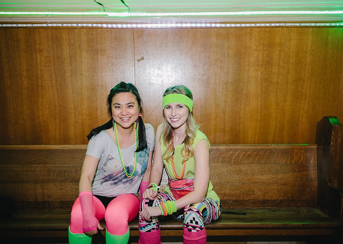two women sit on a church pew in brightly colored clothes