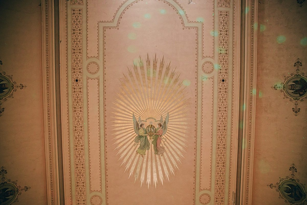 painted ceiling detail—angels in a sunburst, with disco lights shining on them