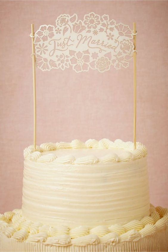 "laser cut white cake topper reads ""Just Married"" with flowers"