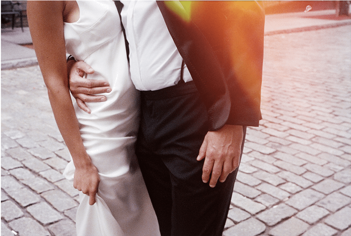 close up photo of a groom pulling his bride to him, in a cobblestone street, on expired film