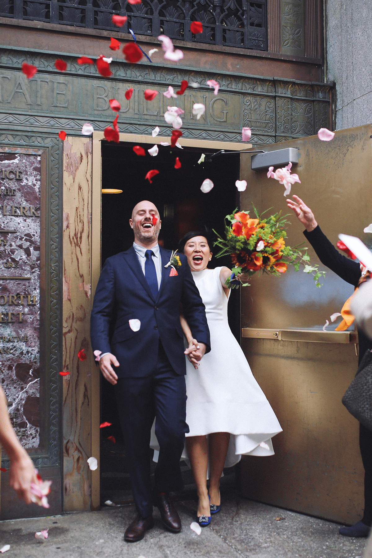 A couple exits their wedding ceremony with flower petals being thrown