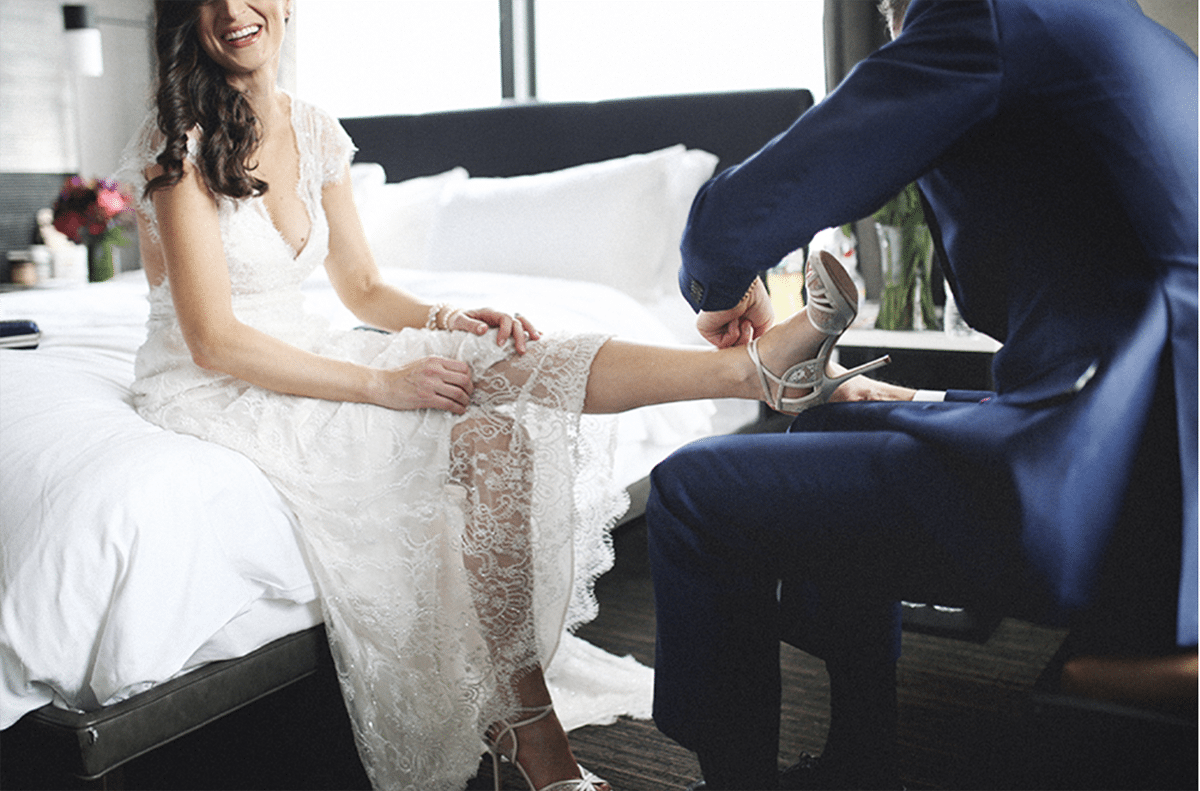 a man helps a bride with her high heels on an urban hotel bed