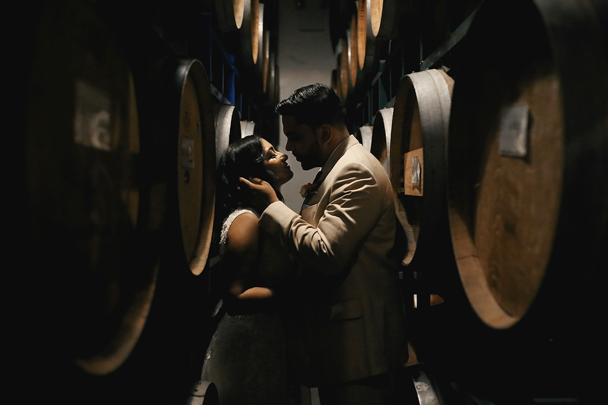 a man cradles a woman's head while standing in between rows of large wooden wine barrels
