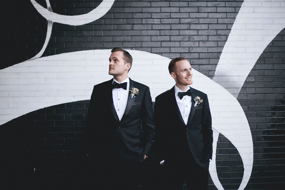 two men stand beside each other wearing tuxes looking in opposite directions, with one man smiling and the other man questioning life