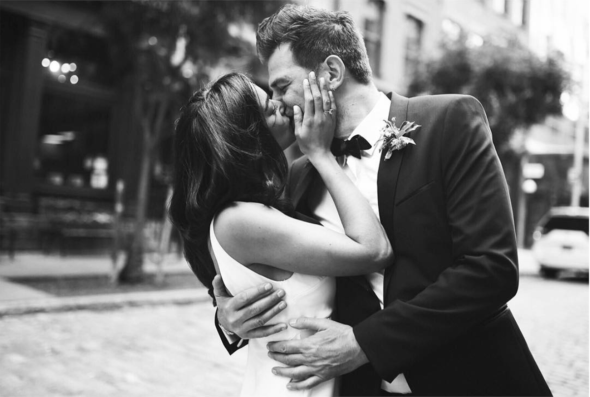 a man and woman kiss in the middle of a street
