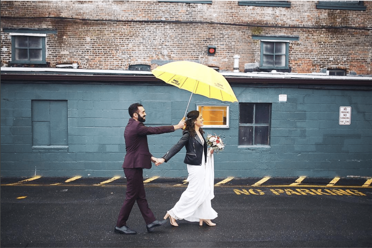 a man holds a yellow umbrella over a woman as they walk down a street