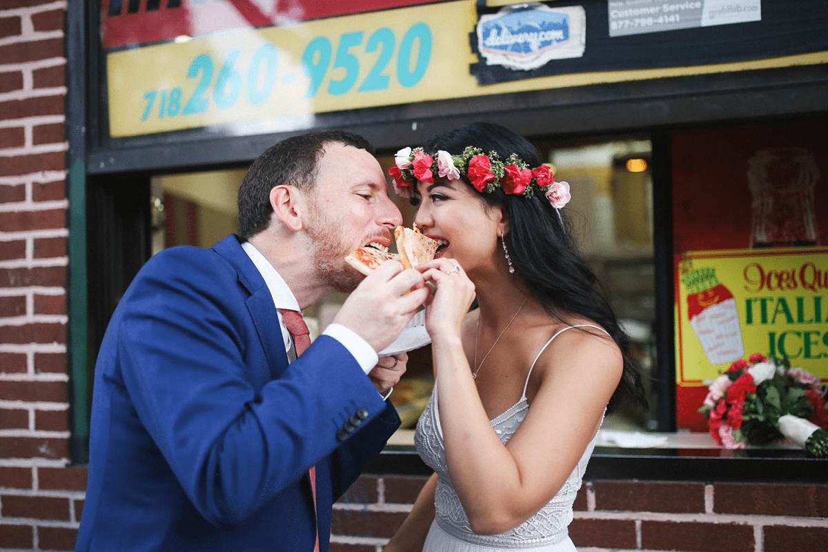 a wedding couple share the same slice of pizza