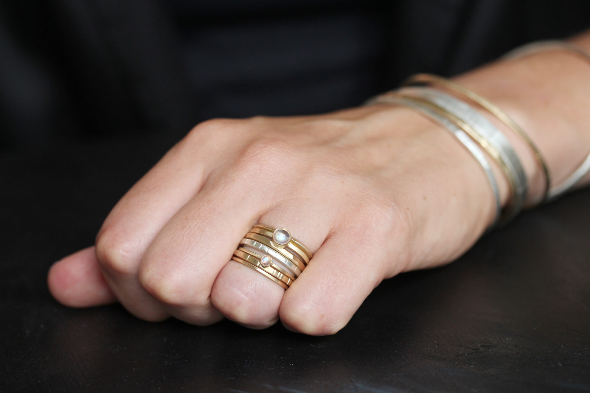 photo of a closed hand with rings and bangle bracelets