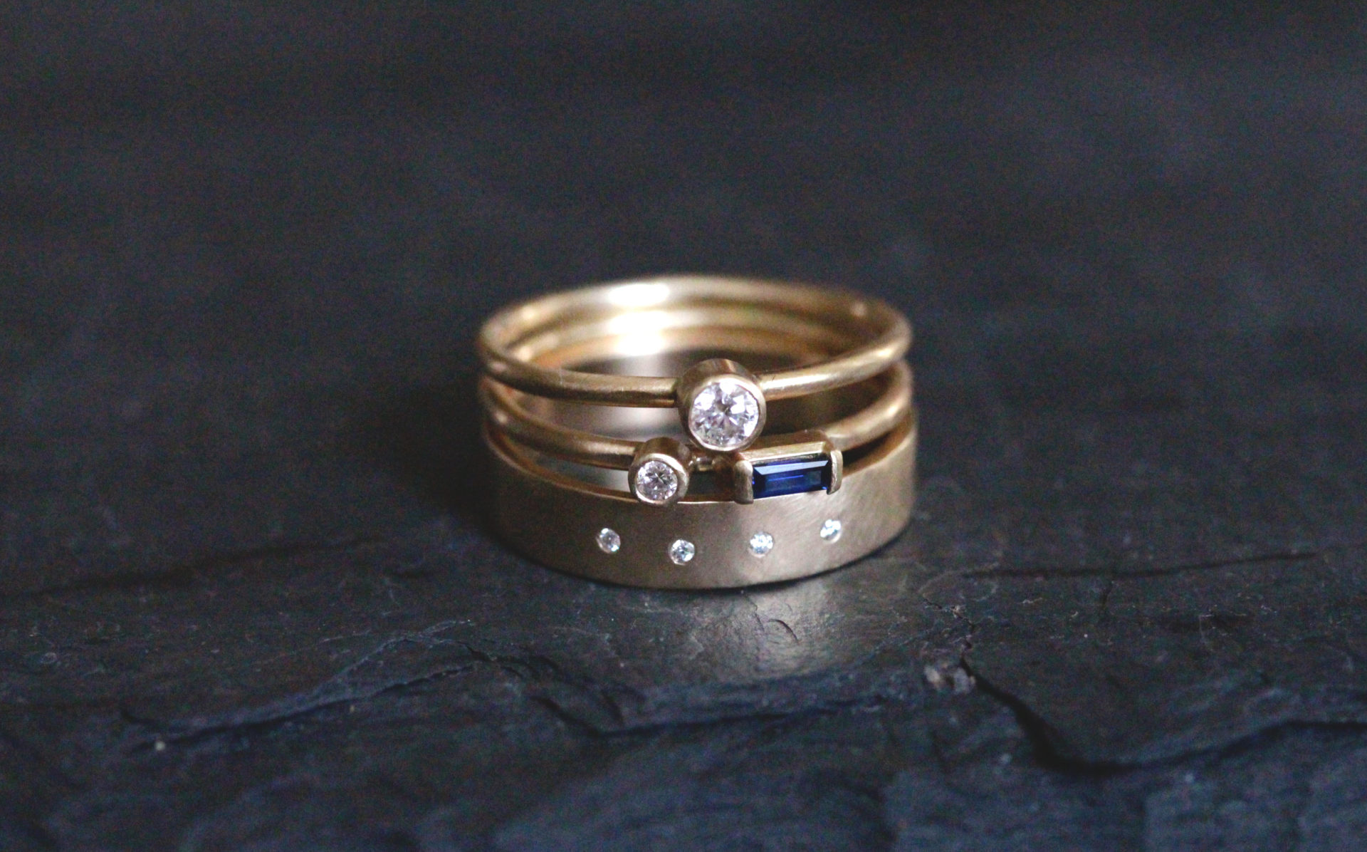 Three rings stacked including the Diamond Highsmith and the Saphire and Diamond Castrée