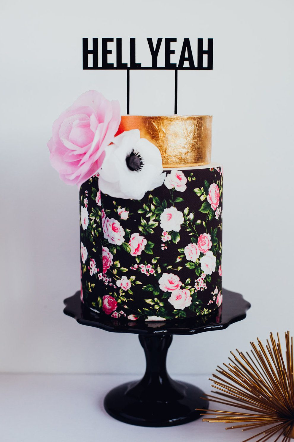 typography topper that says hell yeah on a gold and floral print tiered cake