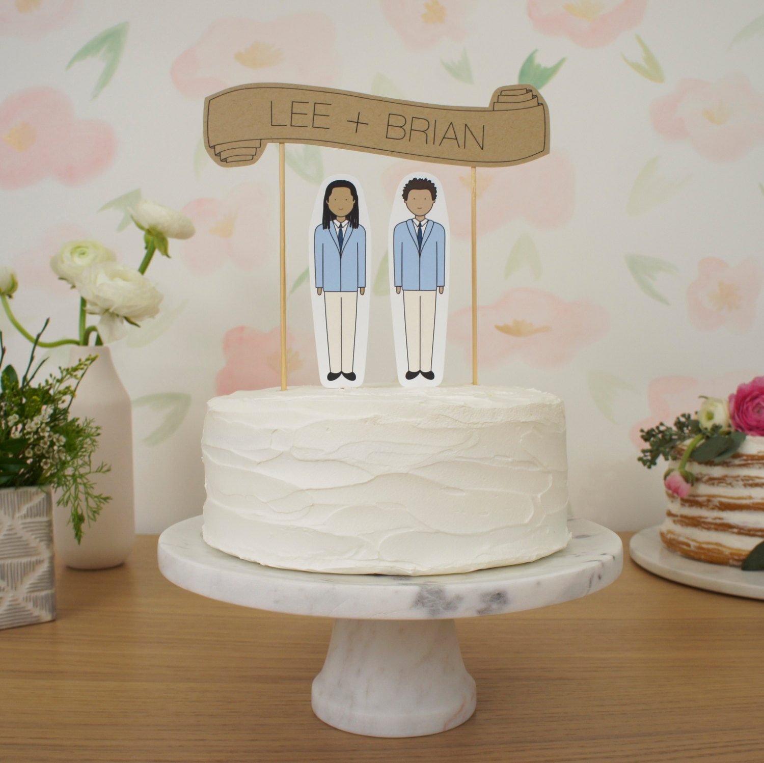 two groom paper dolls on wedding cake