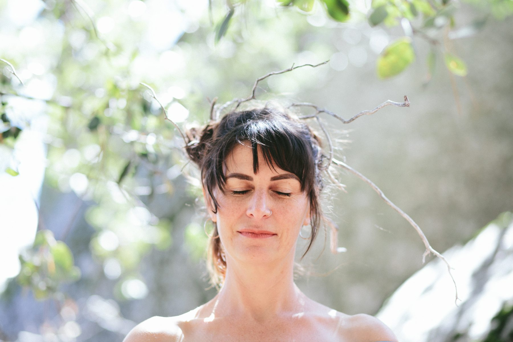 a woman with twigs in her hair, alive