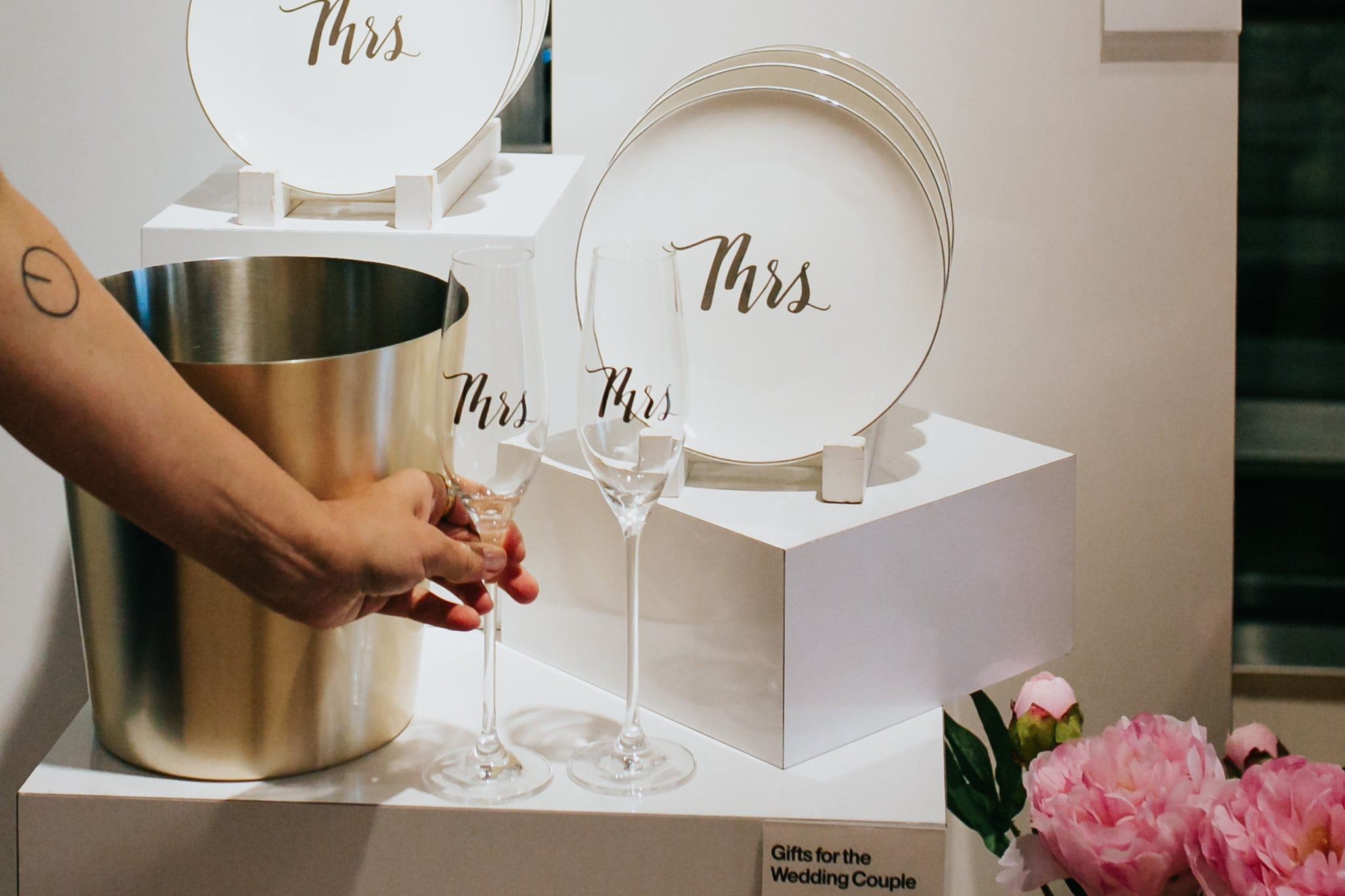 arm reaching for a mrs champagne flute a a crate and barrel private registry event