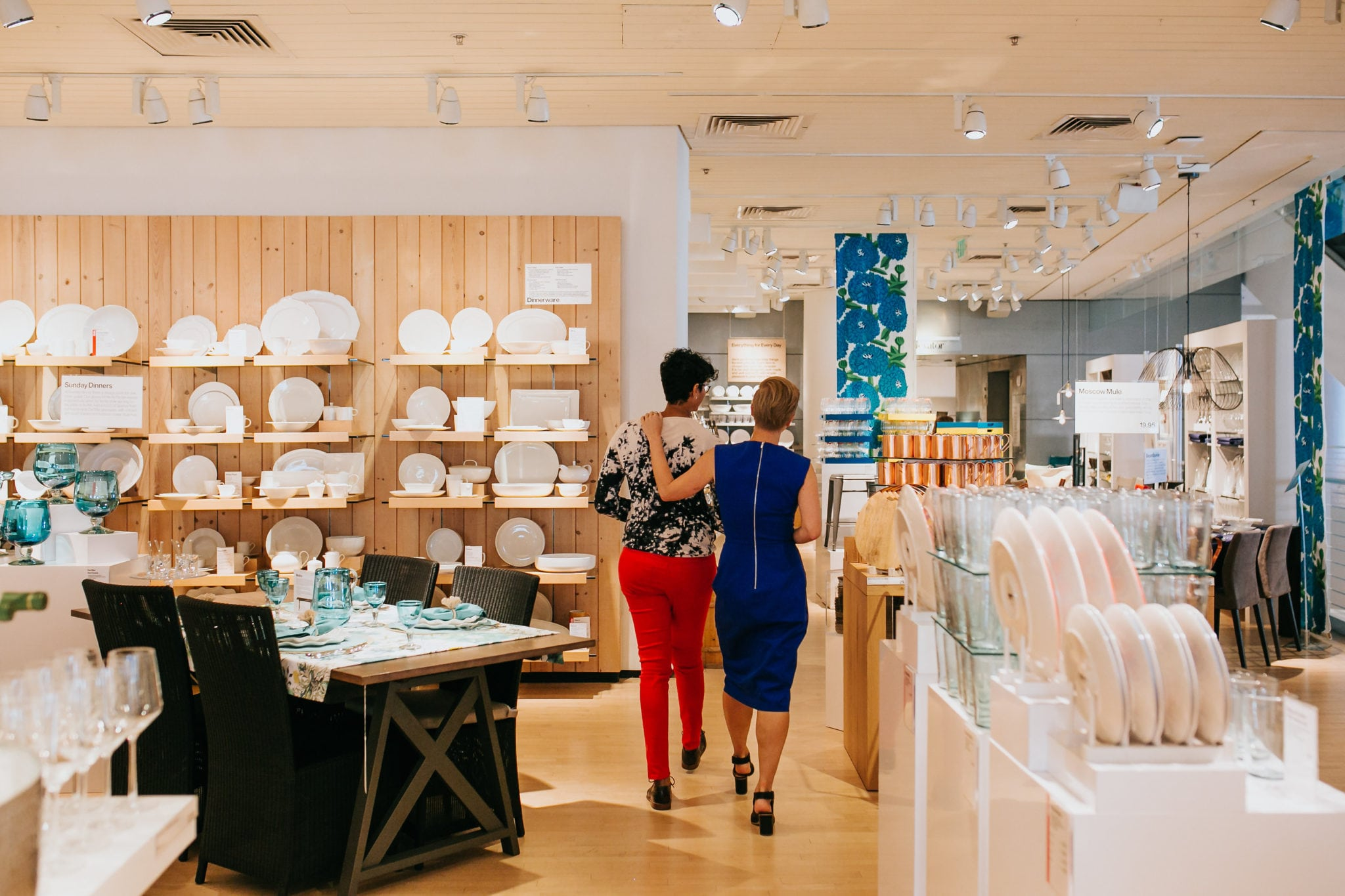 two women embracing while walking through a crate and barrel LGBTQ private registry event