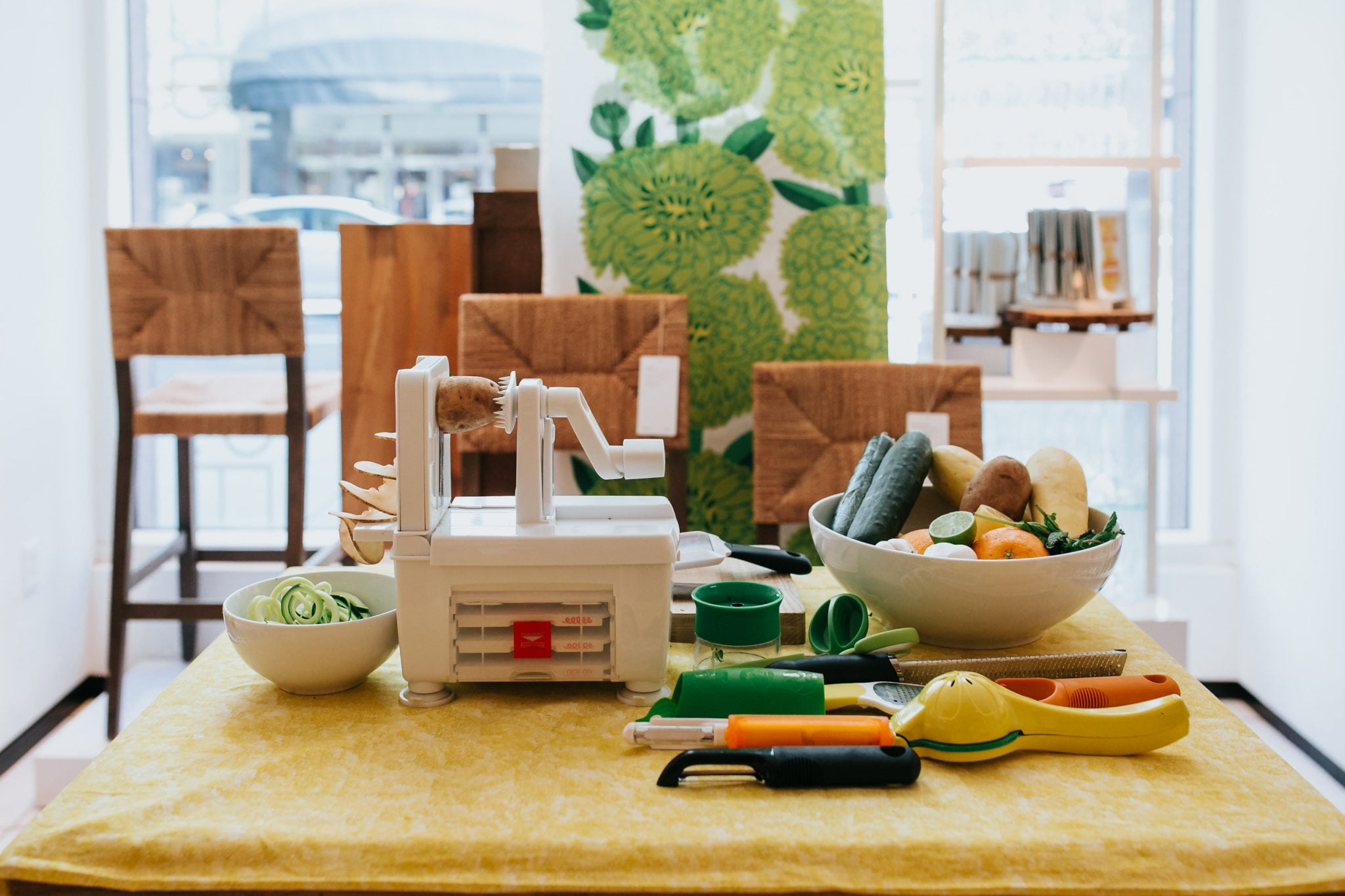a crate and barrel vegetable spiralizer on a table surrounded by fresh vegetables